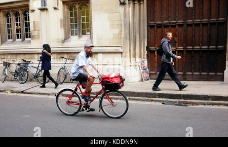 Oxford Oxfordshire UK -  Postman on his bicycle in city centre - Stock Photo