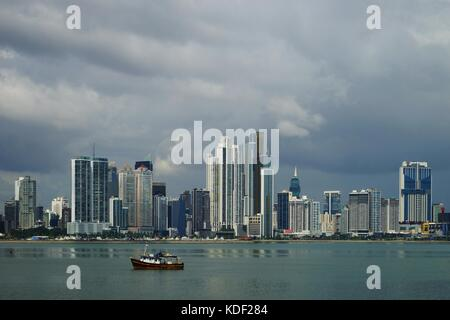 View of Panama City Over Panama Bay with skyline and a fishing boat on the foreground - Stock Photo