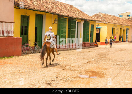 Cuban cowboy rides  horse  past th brigtly coloured l houses on the  cobbled  streets of Trinidad, Cuba, Caribbean - Stock Photo
