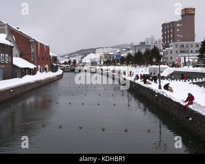 Workers preparing lanterns for the Otaru Winter lightup event and tourists enjoying the scene at Otaru Canel, Hokkaido, - Stock Photo