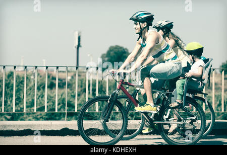 Bike ride young family with two kids in a summer day - Stock Photo