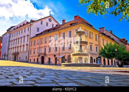 City of Ljubljana fountain on sun beams and street architecture view, capital of Slovenia - Stock Photo