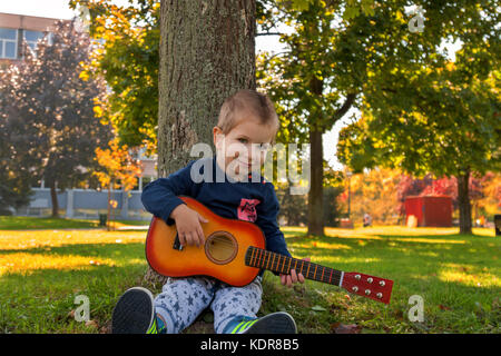 Small boy holding acoustic guitar while sitting leaned on a tree - Stock Photo