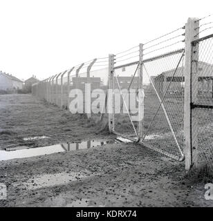 1960s, historical, England, UK, chain link fencing with barbed wire on top and locked gates protect and block any - Stock Photo
