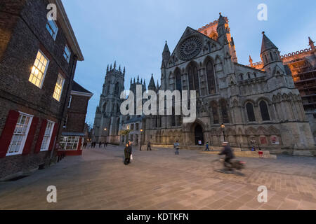 Evening in York centre  - south entrance to magnificent York Minster taken from the piazza where people walk & cycle - Stock Photo