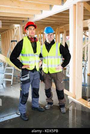Full length portrait of carpenters in protective clothing at construction site - Stock Photo