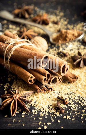 Christmas spices and baking ingredients. Cinnamon sticks, anise stars, nutmeg, cardamom, cloves, brown sugar and - Stock Photo