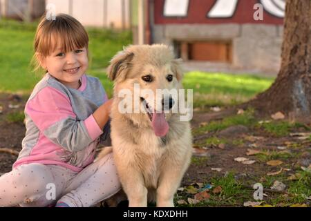 Portrait of a young blond girl child cuddling white puppy outdoors in the park - Stock Photo