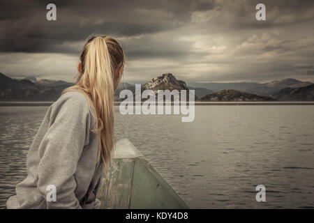 Woman traveler sailing on boat towards shore with with Mountains landscape on horizon in overcast day with dramatic - Stock Photo
