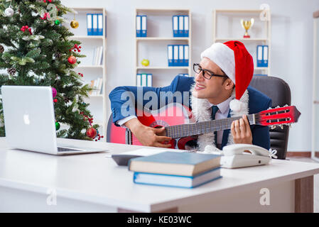 Businessman celebrating christmas holiday in the office - Stock Photo