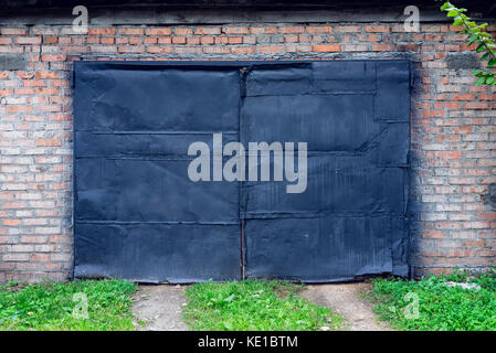 Old painted black paint on garage in nature. Black door in a building against a brick wall. A green lawn path leads - Stock Photo