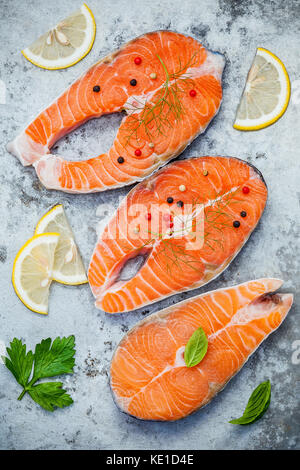 Fresh salmon fillet sliced flat lay on shabby metal background. Raw salmon fillet and ingredients parsley ,sweet - Stock Photo