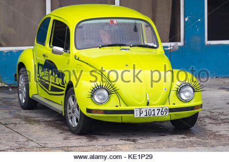 VW compact car with fake lashes attached to the headlights.  Small yellow car in front of blue building with NostalgiCar - Stock Photo