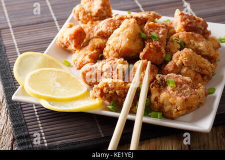Portion fried chicken karaage with lemon and onion close-up on a plate on the table. horizontal - Stock Photo