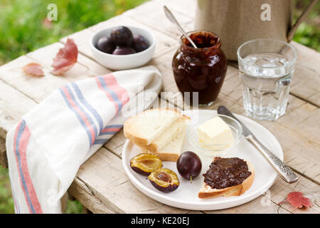 Toasts with plum chocolate jam. Breakfast in the garden. Rustic style, selective focus. Horizontal. - Stock Photo