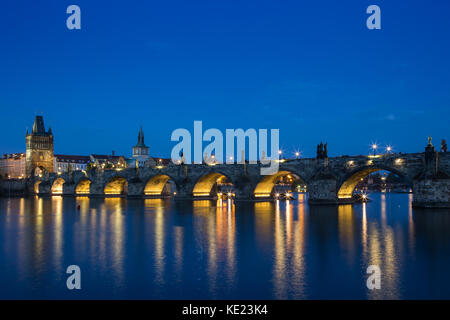 Lit Charles Bridge (Karluv most) and old buildings at the Old Town and their reflections on the Vltava River in - Stock Photo