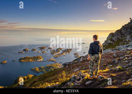 Hiker standing at the top of mount Festvagtinden on Lofoten islands in Norway - Stock Photo