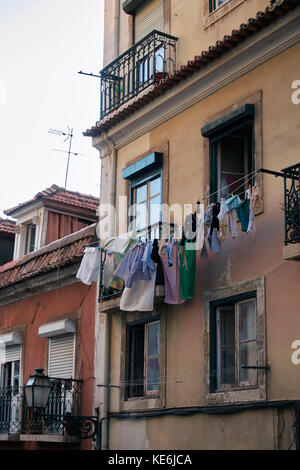 clothes hung out to dry in a facade of building in Lisbon, Portugal - Stock Photo