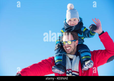 Attractive family having fun in a winter park on mountain - Stock Photo