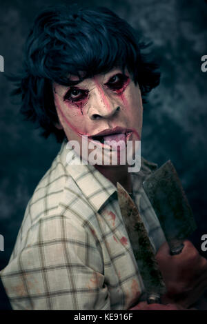 closeup of a scary disfigured man holding some rusty and bloody cleaver and knife in his hands - Stock Photo