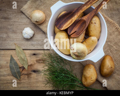 Fresh organic potatoes in hemp sake bag with ingredients and herbs on rustic wooden table preparation for cooking. - Stock Photo
