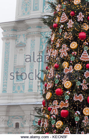 Decorated Christmas tree with toys and cookies in front of the cathedral under the snow - Stock Photo