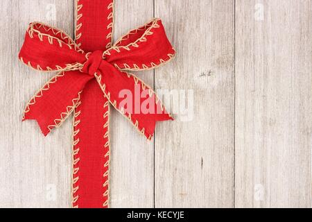 Rustic red Christmas bow and ribbon side border, above view on an old white wood background - Stock Photo