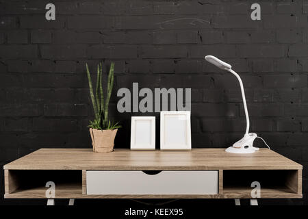 close up view of empty photo frames, plant in flowerpot and table lamp on wooden table - Stock Photo