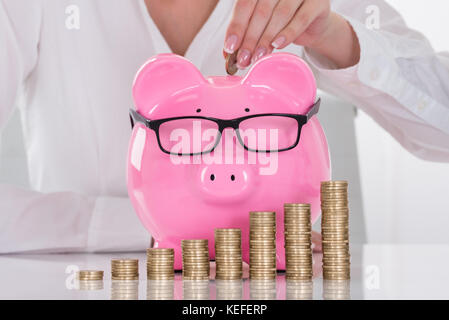 Close-up Of A Female's Hand Inserting Coin In Piggybank - Stock Photo