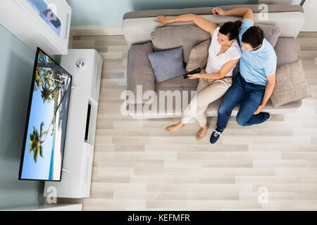 High Angle View Of Young Couple Watching Movie On Television At Home - Stock Photo