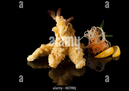 shrimp in tempura with lemon slices and salad on a black background with reflection - Stock Photo
