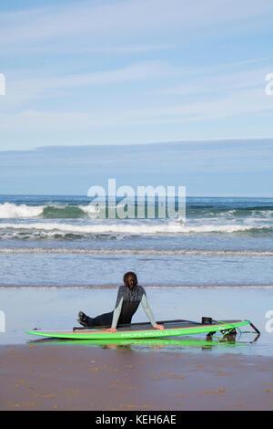 Surfing on Bamburgh beach, Northumberland, England, UK - Stock Photo