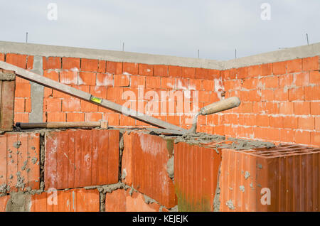 home buliding site. Spirit level, hammer and  howel putty, knife, construction site of clay bricks blocks home and - Stock Photo