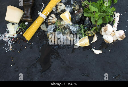 Ingredients for cooking Spaghetti vongole. Clams on chipped ice, raw pasta, Parmesan cheese, garlic, parsley and - Stock Photo