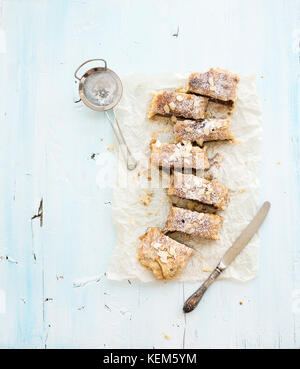 Homemade apple and almond strudel on baking paper over light blue wooden backdrop - Stock Photo
