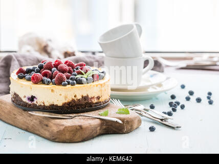 Cheesecake with fresh raspberries and blueberries on a wooden serving board, plates, cups, kitchen napkin, silverware - Stock Photo