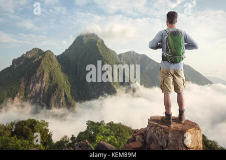 Hiker in front of a tropical mountain panorama - Stock Photo