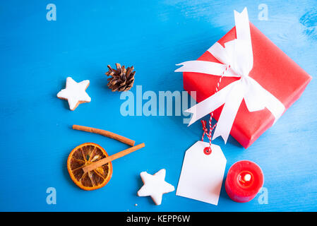 Xmas image with cinnamon sticks, star shaped cookies, dried orange, a lit candle and a lovely red gift tied with - Stock Photo