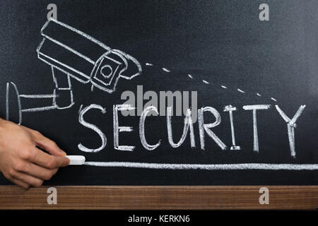 Close-up Of A Person Hand Showing Security Concept On Blackboard - Stock Photo
