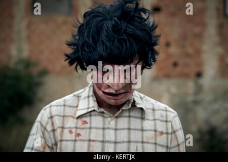 closeup of a scary disfigured man looking down wearing a ragged and dirty shirt with stains of blood, in front of - Stock Photo