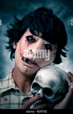 closeup of a scary disfigured man wearing a ragged and dirty shirt with stains of blood, holding a skull in his - Stock Photo