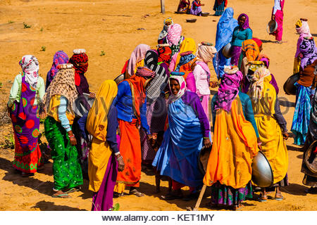 Rajasthani women in bright colors working (carrying dirt) at a construction project along the Jaipur-Agra Road, - Stock Photo