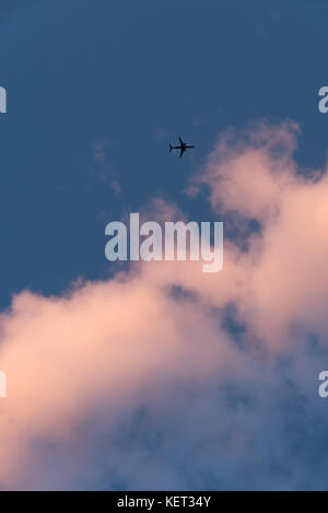 Overhead jet approaching sunset clouds against a deep blue sky. - Stock Photo