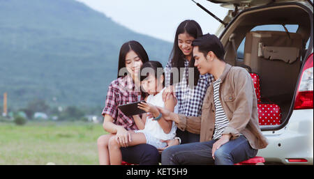happy little girl playing ukulele with asian family sitting in the car for enjoying road trip and summer vacation,soft - Stock Photo