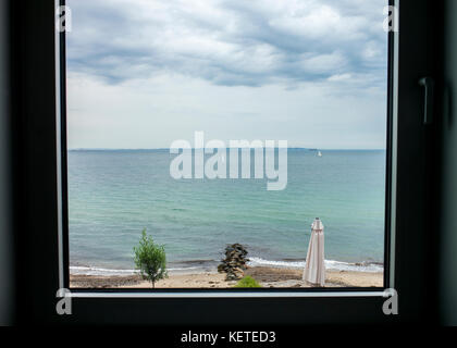 view of sailing boats and sea through window at Helnan Marselis Hotel,Denmark - Stock Photo