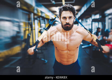 Young handsome man doing exercises in gym - Stock Photo
