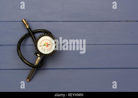 Tyre Inflater with air pressure gauge on blue wooden boards - Stock Photo