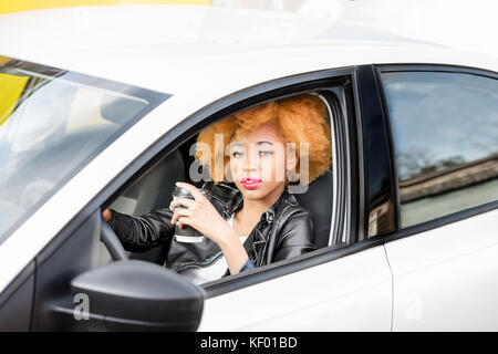 Portrait of a beautiful african woman in the car - Stock Photo
