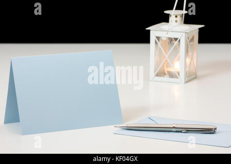Still life with envelope, paper card and pen in front of burning candle in lamp on white board table and black background - Stock Photo