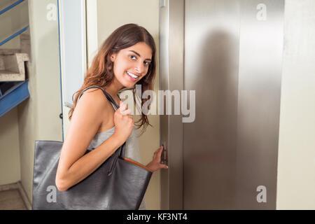 Smiling Young Woman With Handbag Using Elevator - Stock Photo